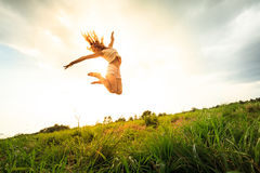 Springendes Mädchen am Feld am Sommer Lizenzfreies Stockfoto