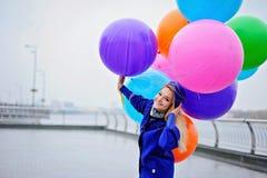 Springendes Mädchen mit bunten Ballonen in ihrer Hand bew?lkter Tag lizenzfreie stockfotos
