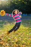 Springendes Mädchen mit Herbstlaub Stockfoto