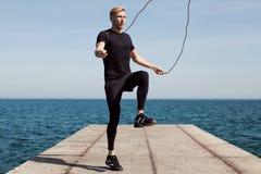 Springendes Seil des Mannes auf Ufergegend Lizenzfreie Stockfotos