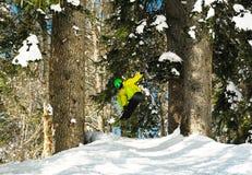 Springendes Zupacken des jungen aktiven Mannes auf Snowboard stockbild