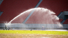 Springer watering the grass on the football field Stock Photography