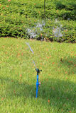 Springer is working and have water spread for green lawn. Stock Image