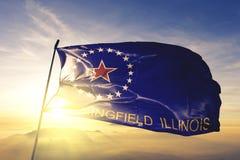 Springfield-Stadthauptstadt von Illinois des Flaggentextilstoffgewebes Vereinigter Staaten, das auf den Spitzensonnenaufgangnebel stockfotografie