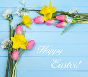 Springflowers on blue wood background. And Happy Easter text stock photo