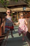 Springhand för två ung systrar - i - hand arkivbild