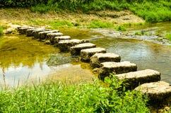 Springplanken die een kleine rivier kruisen Royalty-vrije Stock Afbeelding