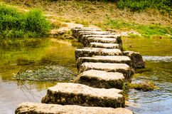 Springplanken die een kleine rivier kruisen Stock Afbeelding