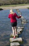Springplankenvrouw die over rivier lopen Stock Afbeeldingen