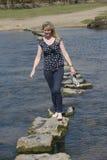 Springplankenvrouw die over rivier lopen Stock Afbeelding