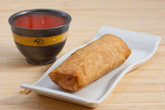 Springroll. One fried egg roll with chopstick and hot sauce Stock Photo