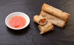 Springroll n sauce. Spring rolls with sweet chili dipping sauce on dark grey slate background Stock Photography