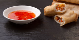 Springroll n sauce. Spring rolls with sweet chili dipping sauce on dark grey slate background Stock Images