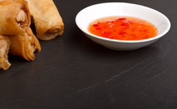 Springroll n sauce. Spring rolls with sweet chili dipping sauce on dark grey slate background Royalty Free Stock Images