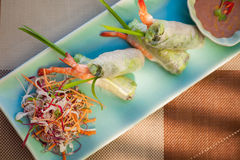 Springroll with vegetables and prawn served with salad and sauce. Asian cuisine.