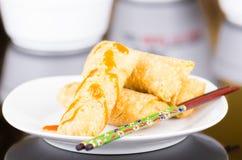 Springrolls που τοποθετείται κομψά στο άσπρο πιάτο με κάποια σάλτσα σόγιας που καλύπτει, chopsticks που βρίσκονται απέναντι Στοκ εικόνα με δικαίωμα ελεύθερης χρήσης