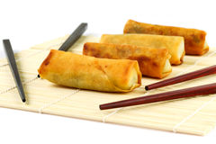Springrolls close up. Chinese springrolls with chosticks on the bamboo mat Royalty Free Stock Photos