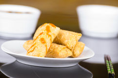 Springrolls elegantly placed on white plate with some soya sauce covering. Chopsticks royalty free stock photography