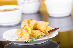 Springrolls elegantly placed on white plate with some soya sauce covering, chopsticks lying across. With figures stock images