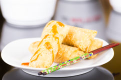 Springrolls elegantly placed on white plate with some soya sauce covering, chopsticks lying across. With green figures royalty free stock image