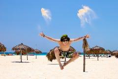 Springt de Appy jonge mens voor vreugde op het strand, tegen blauwe hemel en oceaan royalty-vrije stock foto