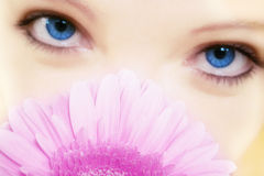 Springtime. A girl is holding a flower in front of her beautiful face Stock Photography