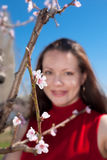 Springtime. Young woman in garden among the blossoming peach trees Stock Photo