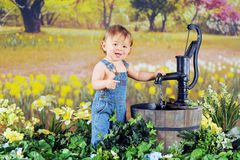 Springtime Baby. An adorable baby boy delightedly playing with a water pump in a field of yellow daffodils Royalty Free Stock Photo