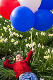 Springtime Balloons. A beautiful young mixed race girl playing with balloons in a field of daffodils royalty free stock photos