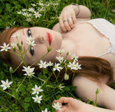 Springtime Beauty. A portrait of a beautiful woman lying down in grass, surrounded by white flowers Stock Images