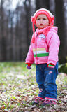 Springtime blonde baby girl. Blonde blue eyed baby girl is playing in the forest Stock Images