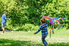 Springtime concept idea, spring background environment,  biology business.Kite in summer boy playing on field, park day,  fun fly stock photos