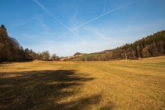 Springtime countryside with meadows, fields, forest, small hills and blue sky royalty free stock image