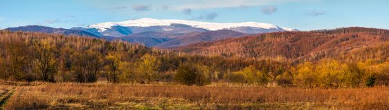Springtime countryside with snowy mountain. In the distance. lovely panorama of Runa mountain in evening royalty free stock image