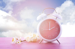 Springtime Daylight Saving Time Clock Concept. Springtime daylight saving time concept with pink clock on pink wood table with blue sky background, and added stock photos