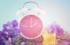 Springtime Daylight Saving Time Clock Concept. Springtime daylight saving time concept with pink clock on pink wood table with blue sky background, with added Stock Photo