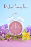 Springtime Daylight Saving Time Clock Concept. Springtime daylight saving time concept with pink clock on pink wood table with blue sky background, with sample royalty free stock photography