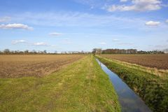 Springtime ditch near plowed fields Royalty Free Stock Images