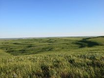 Springtime in the Flinthills of Kansas. This photo is taken in the spring after the open range have been burnt and are regrowing into this beautiful green Stock Photos