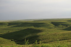 Springtime in the Flinthills of Kansas. This photo is taken in the spring after the open range have been burnt and are regrowing into this beautiful green Stock Image