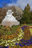 Springtime flowers and white statue in the park. LYON, FRANCE, March 23, 2018 : Parc de la Tete d`Or in Lyon is a large urban park with an area of approximately Royalty Free Stock Photos