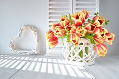 Springtime greeting card design with bunch of red tulips and spring decorations on light wood. En background stock images