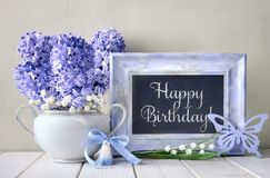 Blue decorations and hyacinth flowers on white table, blackboard. Springtime `Happy Birthday` postcard design for a boy. Blue decorations and hyacinth flowers on Royalty Free Stock Images