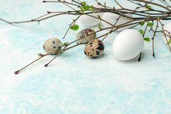 Springtime holiday seasonal background - eggs and fresh greenery branches on light white-blue background, copy space, simple. Concept stock photo