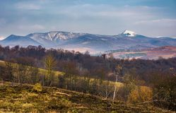 Springtime landscape in Carpathian mountains. Mountain ridge with Pikui snowy peak in the distance royalty free stock photos