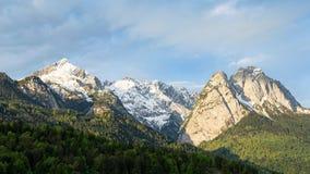 Springtime morning snowy Alps mountains panoramic scenic view Stock Photos