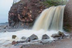 Springtime Nova Scotia coastline in June. Waterfalls from a cliff onto rocky pebble beach. Royalty Free Stock Photo