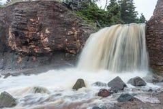 Springtime Nova Scotia coastline in June. Waterfalls from a cliff onto rocky pebble beach. Stock Photography