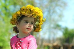 Close up portrait of a cute laughing two years old girl wearing a dandelion wreath. Springtime portrait of a cute two years old girl posing with a dandelion Royalty Free Stock Images