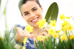 Springtime, smiling woman in garden takes care of flowers Stock Photo